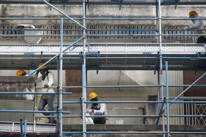 Construction workers operating on scaffolding on Jan 18, 2013. Growth in the service and construction industries in Singapore is expected to remain tepid, on the back of a subdued property market and a marked slowdown in tourism inflows. -- ST PHOTO: