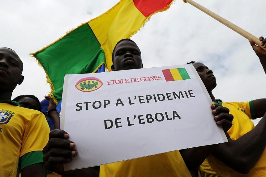 "Players of the '""L'Etoile de Guinee"" football team pose with a sign reading ''Stop the ebola epidemic'' prior to a football tournament gathering youth from Guinea near the Koumassi sports centre in Abidjan on August 10, 2014. The  West African E"