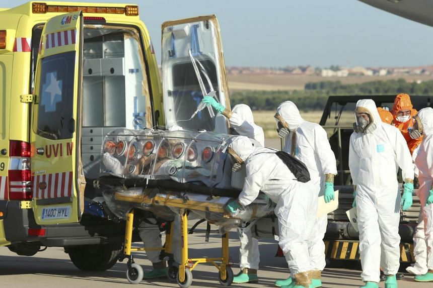 Health workers put Ebola patient, Spanish priest Miguel Pajares, into an ambulance on the tarmac of Torrejon airbase in Madrid, after he was repatriated from Liberia for treatment in Spain. Should we worry if a Singaporean gets infected? -- PHOTO: RE