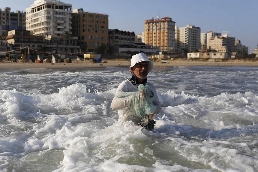 A fisherman prepares to cast his net in Gaza City's main beachfront August 10, 2014. Israel and the Palestinians agreed on Sunday to an Egyptian proposal for a new 72-hour ceasefire in Gaza starting at 9pm GMT.-- PHOTO: REUTERS