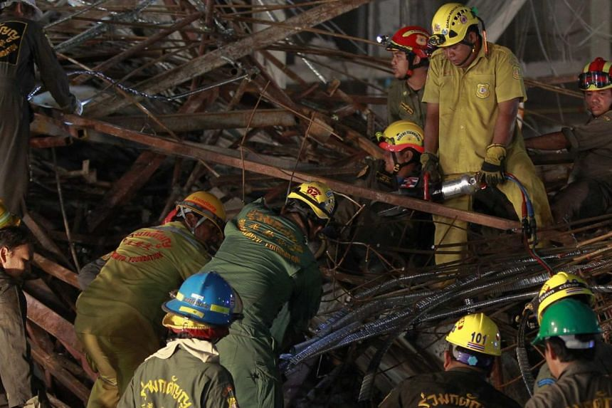 Rescue workers search through the rubble of a collapsed condominium building, which had been under construction, in Pathum Thani province, on the outskirts of Bangkok, August 11, 2014. The six-storey condominium building in Thanyaburi district collap