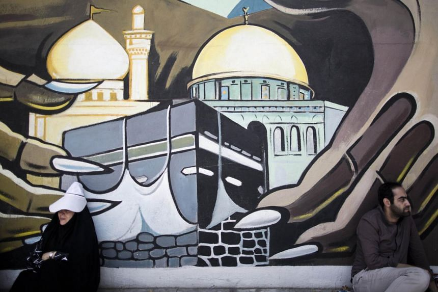 An Iranian man and woman sit under a mural bearing the image of the Kaaba of Mecca and Dome of the Rock of Jerusalem at Palestine square in Tehran on July 25, 2014 to mark Quds (Jerusalem) Day. PHOTO: AFP