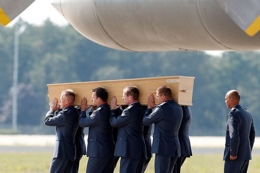 Men carry a coffin containing human remains collected over the last couple of days at the crash site of Malaysia Airlines flight MH17 in Ukraine, upon its arrival at the Eindhoven Airport, the Netherlands on Aug 4, 2014. -- PHOTO: AFP