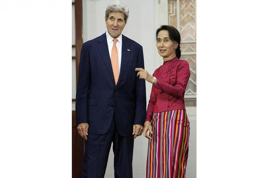 US Secretary of State John Kerry stands next to Myanmar opposition leader Aung San Suu Kyi as she gestures during a photo session before their meeting at her residence in Yangon on Aug 10, 2014.-- PHOTO: REUTERS