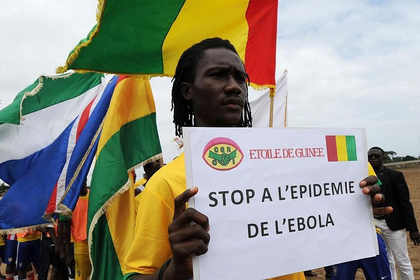 Players of the ''L'Etoile de Guinee'' football team pose with a sign reading ''Stop to the ebola epidemic'' prior to a football tournament gathering youth from Guinea near the Koumassi sports center in Abidjan on Aug 10, 2014.As the world scram
