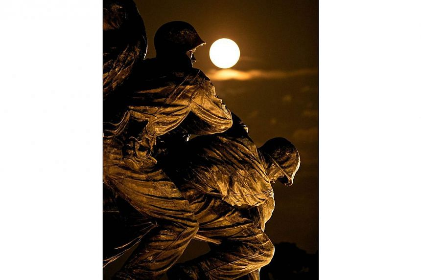 A supermoon rises above the U.S. Marine Corps War Memorial on August 10, 2014 in Arlington, Virginia. -- PHOTO: AFP