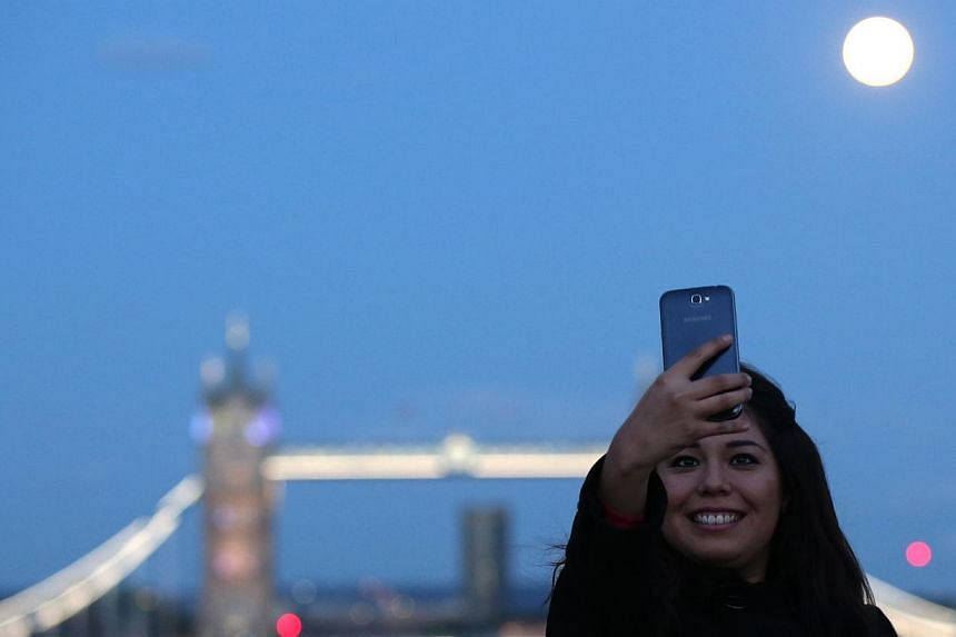 A woman takes a selfie as the supermoon rises over Tower Bridge in London. -- PHOTO: REUTERS