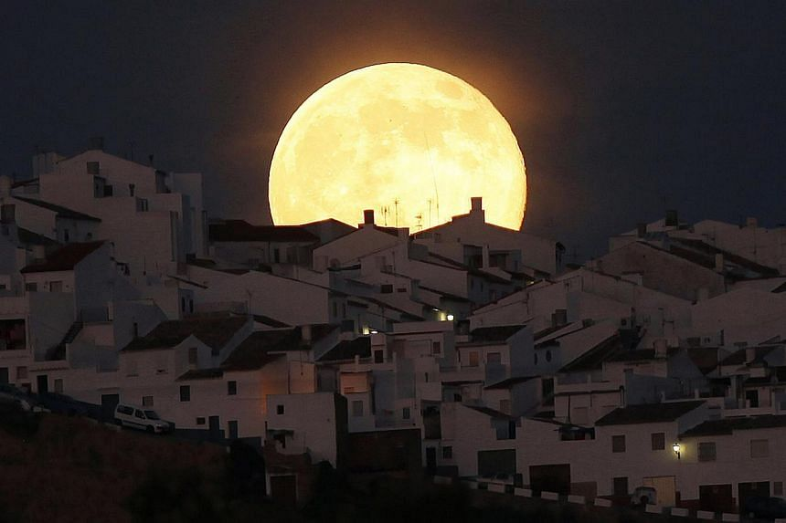 The Supermoon rises over houses in Olvera, in the southern Spanish province of Cadiz. -- PHOTO: REUTERS