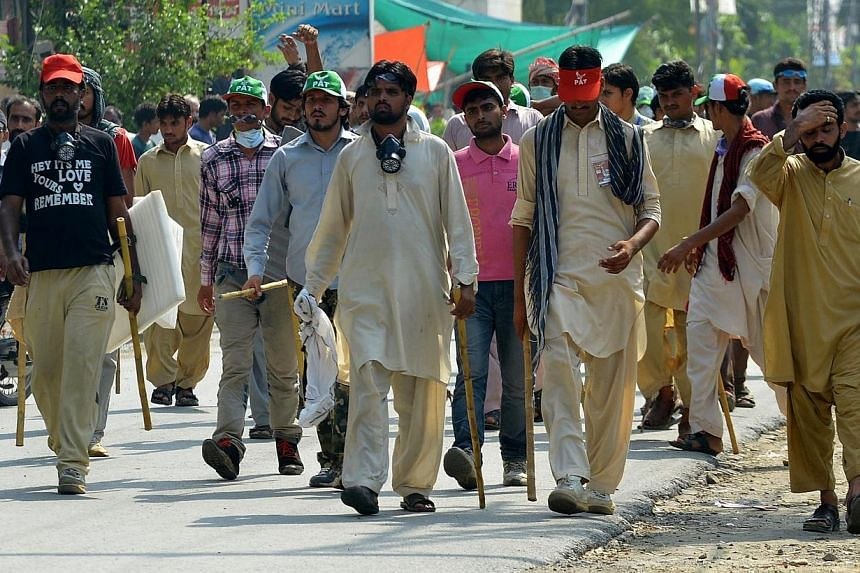 Pakistani upporters of cleric Tahir-ul-Qadri arrive outside his house in Lahore on Aug 10, 2014. -- PHOTO: AFP