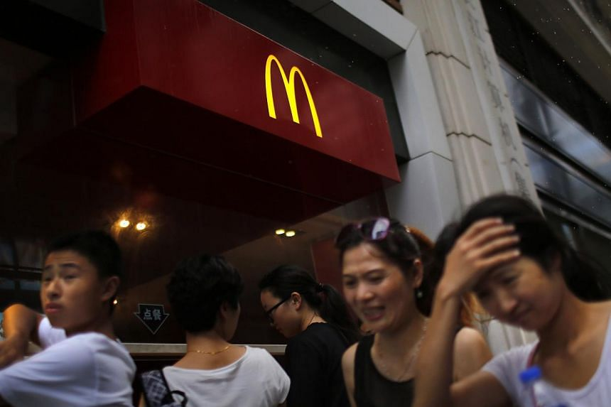 People walk by a McDonald's store in downtown Shanghai on July 31, 2014. Five fast food chains including McDonald's and Yum Brands Inc have published details of their suppliers on their Chinese websites following a request from Shanghai authorit