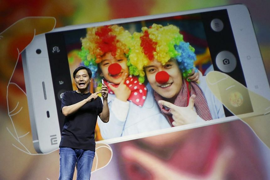 Lei Jun, founder and chief executive officer of China's mobile company Xiaomi, demonstrates the new features of the new Xiaomi Phone 4 at its launching ceremony, in Beijing on July 22, 2014.Xiaomi Inc said it had upgraded its operating system t