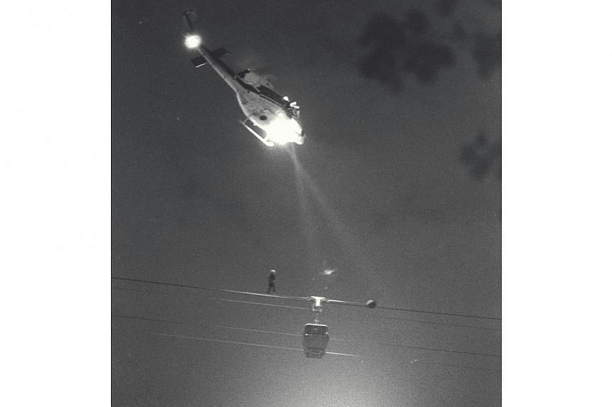 Spotlights focus on a stranded cable car over Keppel Road as a RSAF helicopter lowers a member of the rescue team towards the car.  -- PHOTO: ST FILE