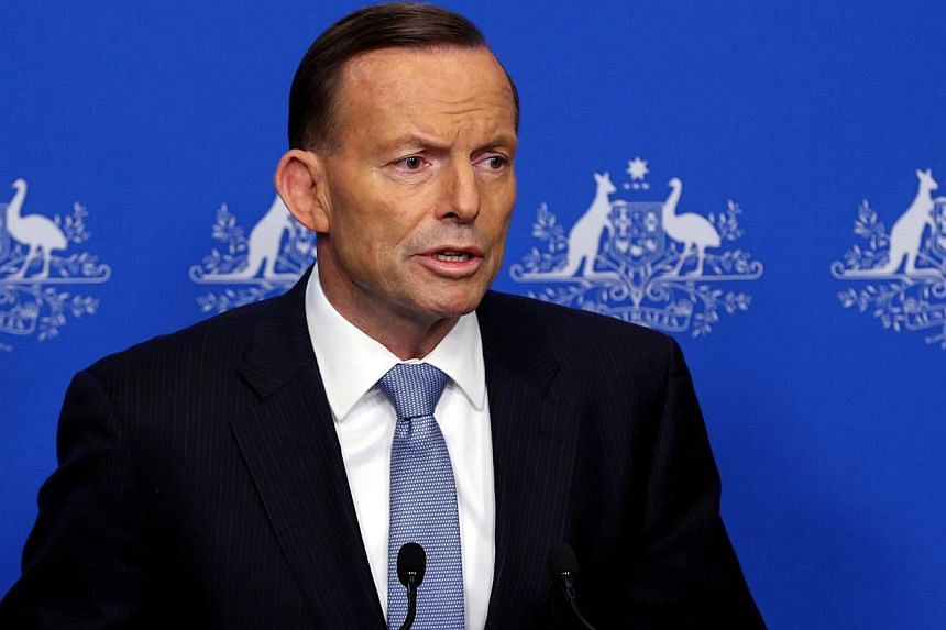 """A shocking image of what is believed to be the young son of an Australian man holding a decapitated head in Syria showed how barbaric the Islamic State (IS) """"terrorist army"""" is, Prime Minister Tony Abbott said on Monday. -- PHOTO: AFP"""