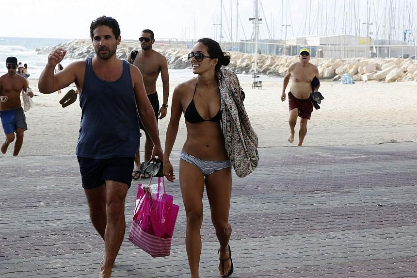 Israelis and tourists running from the beach to take cover in a nearby hotel in the costal city of Tel Aviv on July 14, 2014 during a rocket attack fired by Palestinian militants from the Gaza Strip. In July, 218,000 visitors were recorded entering I