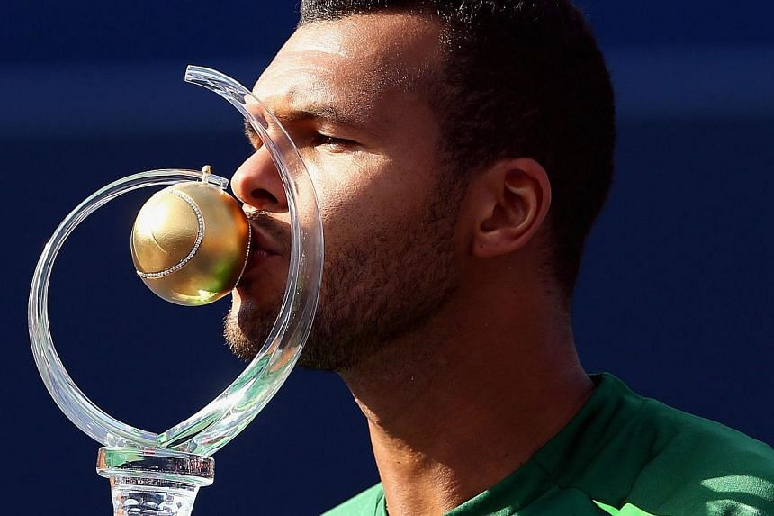 Jo-Wilfried Tsonga of France kisses the Rogers Cup trophy after his win against Roger Federer of Switzerland during the Rogers Cup at Rexall Centre at York University on August 10, 2014 in Toronto, Canada. -- PHOTO: AFP