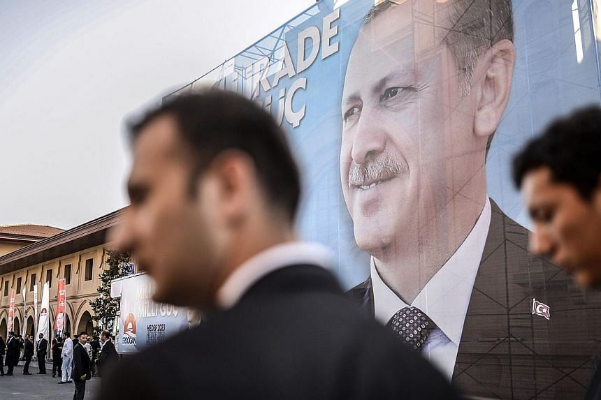 Security officers wait in front of a giant poster bearing a picture of Turkish prime minister and presidential candidate Recep Tayyip Erdogan on August 10, 2014, in Istanbul. Mr Erdogan won Turkey's first popular presidential election on Sunday wit