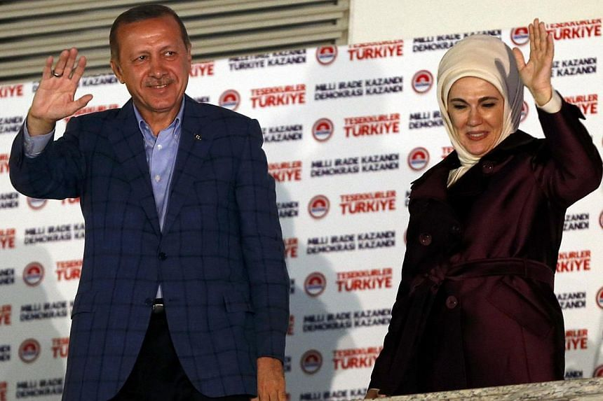 Turkey's Prime Minister Tayyip Erdogan and wife Ermine wave to supporters as he celebrates his election victory in front of the party headquarters in Ankara on August 10, 2014. Mr Erdogan secured his place in history as Turkey's first directly electe