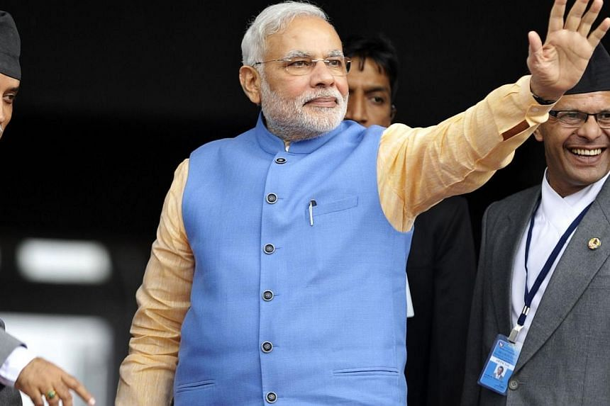 Indian Prime Minister Narendra Modi (centre) waves to unseen wellwishers as he arrives to meet with Nepalese Prime Minister Sushil Koirala following a meeting at the prime minister's office in Kathmandu on Aug 3, 2014.Mr Modi was the first Indi