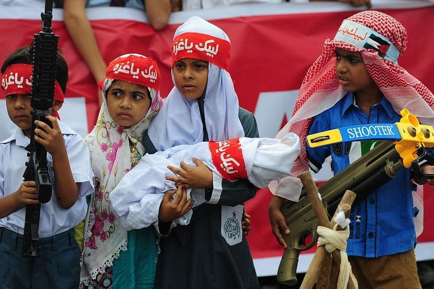 Pakistani children hold toy weapons during a demonstration organised by the fundamentalist Islamic political party Jamaat-i-Islami (JI) in Karachi on Aug 12, 2014, against Israeli military action in Gaza.-- PHOTO: AFP
