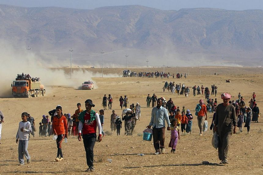 Displaced people from the minority Yezidi sect, fleeing violence from forces loyal to the Islamic State in Sinjar town, walk towards the Syrian border, on the outskirts of Sinjar mountain, near the Syrian border town of Elierbeh of Al-Hasakah Governo