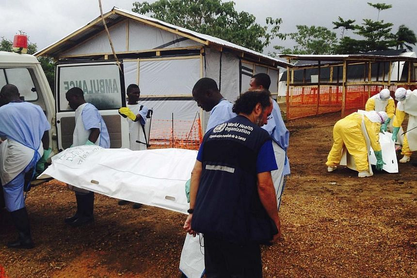 Volunteers carry bodies in a centre run by Medecins Sans Frontieres for Ebola patients in Kailahun on Aug 2, 2014. -- PHOTO: REUTERS
