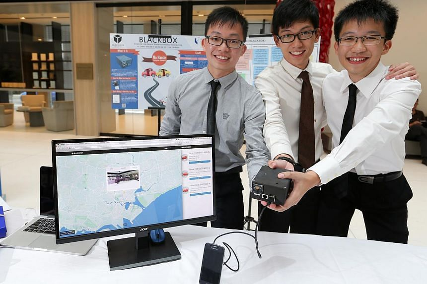 SMU undergraduate Clarence Ngoh (centre) and full-time national servicemen Kong Yu Jian (left) and Wong Wai Tuck with their invention, the BlackBox, a car crash detection system that alerts emergency responders. -- ST PHOTO: ONG WEE JIN
