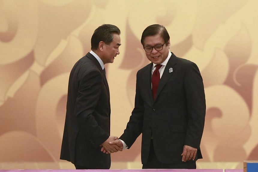 China's Foreign Minister Wang Yi and Thailand's Foreign Ministry Permanent Secretary Sihasak Phuangketkeow (R) shake hand as they attend the Asean-China ministerial meeting at Myanmar International Convention Centre (MICC) in Naypyitaw on August 9, 2