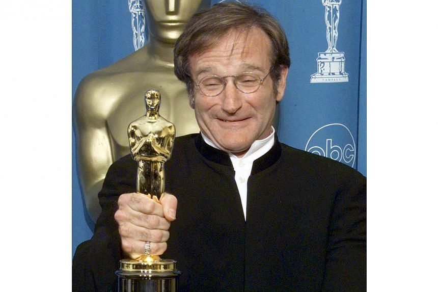 Robin Williams, winner for Best Supporting Actor in Good Will Hunting, posing for photographers with the Oscar at the 70th Annual Academy Awards at the Shrine Auditorium in Los Angeles on March 23, 1998. -- PHOTO: REUTERS