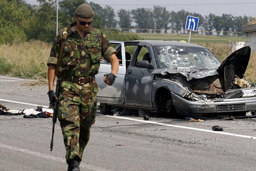 A Ukrainian soldier walks past a damaged car which was used by pro-Russian militants who tried to break through the checkpoint of Ukrainian forces, near the eastern Ukrainian city of Donetsk on August 11, 2014. With Ukraine reporting Russia has masse