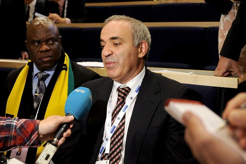 Russian former chess champion Garry Kasparov (right) answers journalists' questions after he lost the presidential election of the International Chess Federation in Tromso, Norway, on August, 11, 2014 in a highly politicised vote. He is seated next t