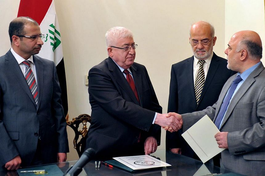 A hand out photograph made available by the offices of Iraqi President on August 11, 2014, shows newly elected Iraqi parliament speaker Salim al-Juburi (left) watching as Iraqi President Fuad Masum (second from left) shakes hands with deputy parliame