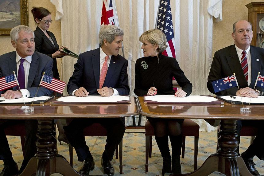 Australian Foreign Minister Julie Bishop (second right) speaks with US Secretary of State John Kerry alongside US Secretary of Defense Chuck Hagel (left) and Australian Defence Minister David Johnston (right) during a signing ceremony for a joint for