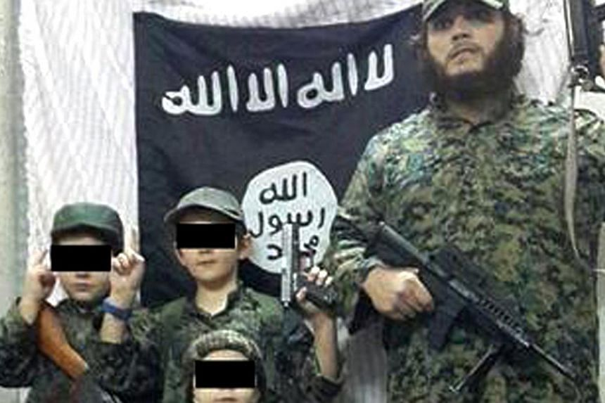Khaled Sharrouf and boys believed to be his sons stand in front of the Islamic State flag. -- PHOTO: TWITTER