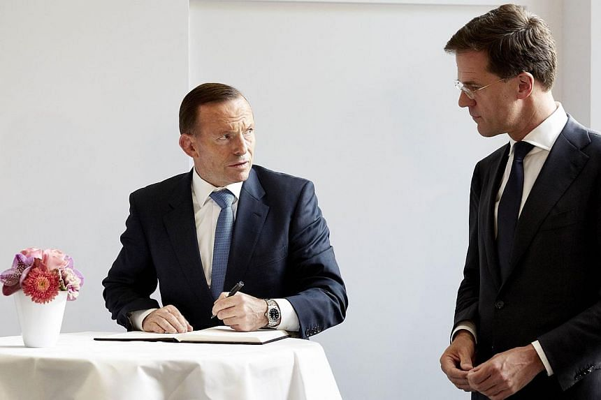 Australian Prime Minister Tony Abbott (left) accompanied by Dutch counterpart Mark Rutte signs a condolence register during his visit to Mr Rutte's official residence Catshuis in The Hague, The Netherlands, on August 11, 2014. Mr Abbott is visiting t