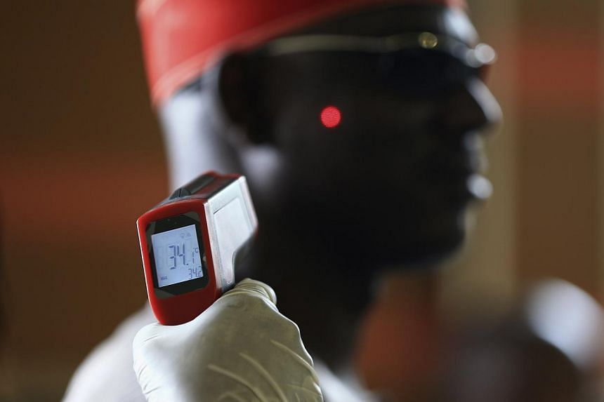 A man has his temperature taken using an infrared digital laser thermometer at the Nnamdi Azikiwe International Airport in Abuja on Aug 11, 2014.-- PHOTO: REUTERS