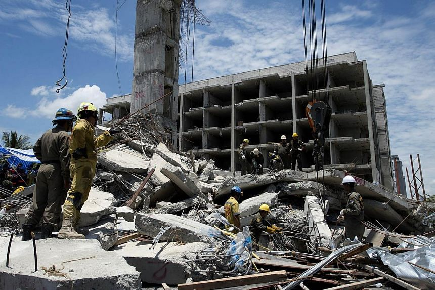 Thai rescue workers use cranes to search for trapped people after a six-storey building under construction collapsed in Pathum Thani province on Aug 12, 2014. Thai rescuers Tuesday pulled a survivor from the rubble of a collapsed building as the
