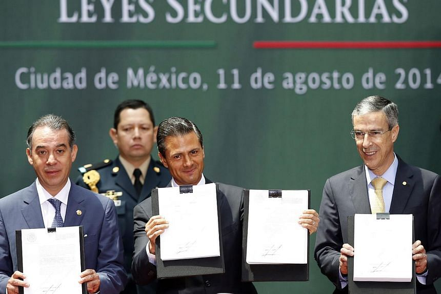 Mexico's President Enrique Pena Nieto (centre), the president of Mexico's Senate Raul Cervantes (left) and president of the Chamber of Deputies Jose Gonzalez hold up a written version of an energy reform at the National Palace in Mexico City August 1