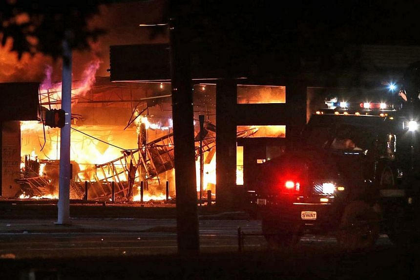 A QuikTrip convenience store burns during a night of rioting in Ferguson, Missouri on August 10, 2014. Police arrested 32 people after rioting and looting erupted in Ferguson, Missouri, late on Sunday and spread to neighbouring towns in protests that