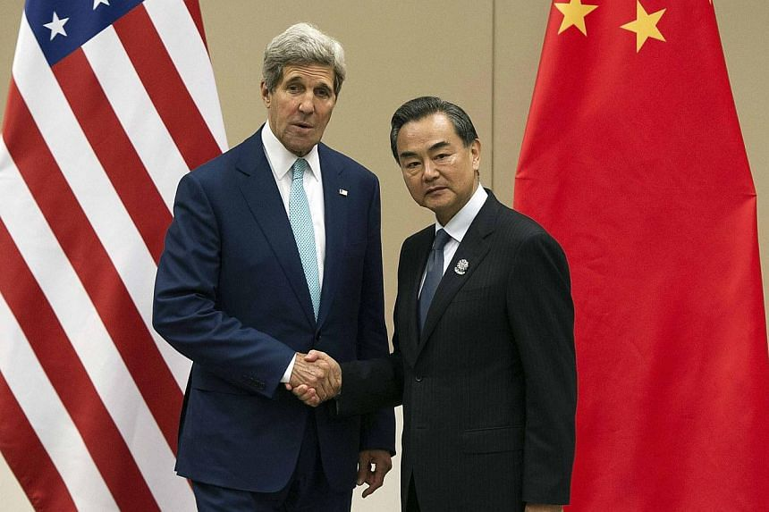 """US Secretary of State John Kerry shaking hands with Chinese Foreign Minister Wang Yi at the Asean Regional Forum in Naypyitaw, Myanmar, on August 9, 2014. Mr Wang suggested the US' aim regarding disputes over the South China Sea might be """"tocre"""