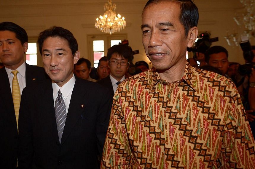 Indonesian President-elect Joko Widodo (right) walks next to Japan's Foreign Minister Fumio Kishida (second left) prior to their meeting in Jakarta on August 12, 2014. Kishida, who is on a two-day visit, held the meeting with Indonesia