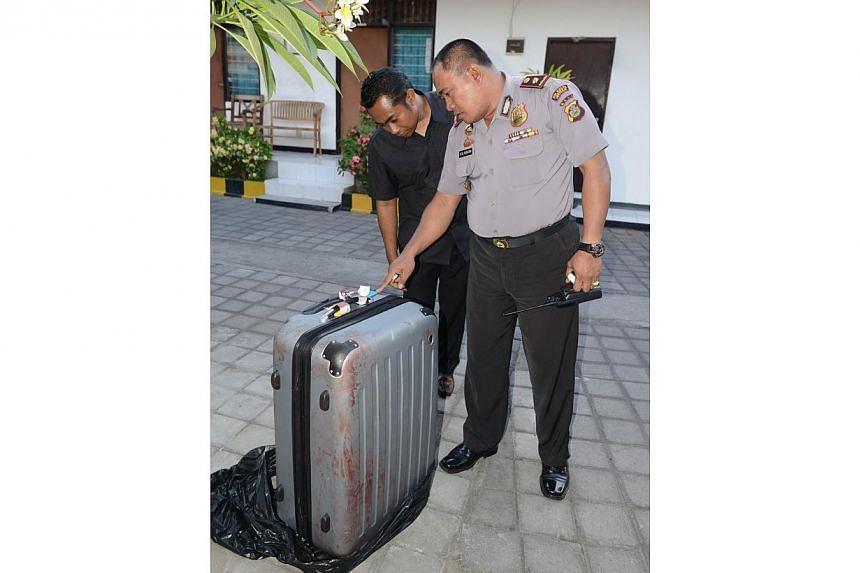 This photo taken on August 12, 2014 shows a policeman (right) looking at a suitcase where the body of a woman was found inside, displayed at a police station in Nusa Dua on the Indonesian resort island of Bali.An American tourist's battered bod