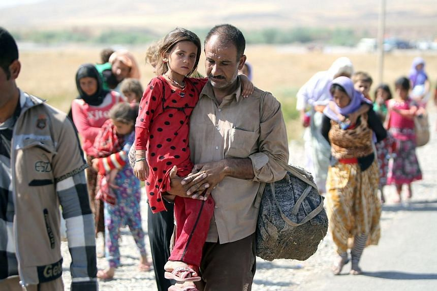 A displaced Iraqi man from the Yazidi community carries his daughter as they cross the Iraqi-Syrian border at the Fishkhabur crossing, in northern Iraq, on Aug 11, 2014. -- PHOTO: AFP