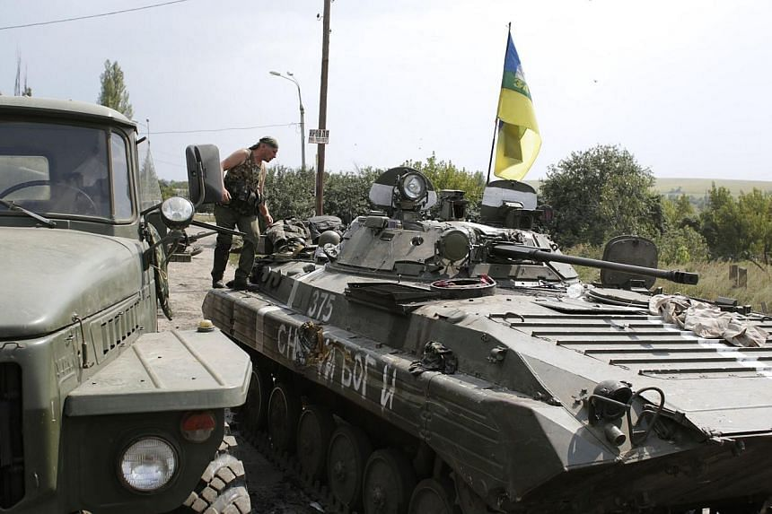 A Ukrainian soldier preparing to refuel his armoured personnel carrier near the eastern Ukrainian city of Donetsk on Monday. Tougher sanctions won't change Russia's approach to Ukraine because Mr Putin is determined that it will eventually become the