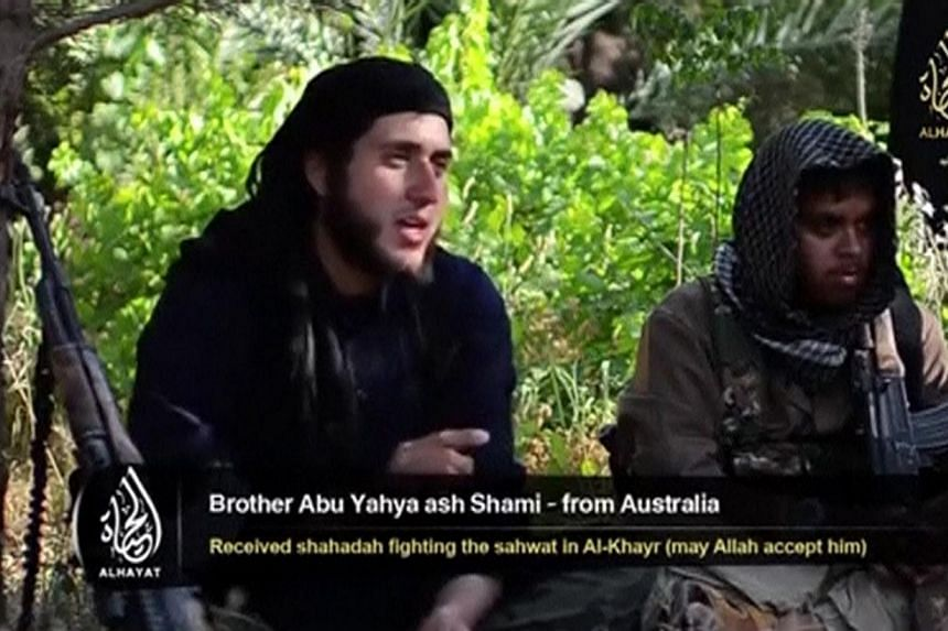 """An Islamist fighter, identified as Abu Yahya al-Shami from Australia (left), speaks in this still image taken undated video shot at an unknown location. Australians are becoming key players in the successful """"social media wars"""" being waged from Iraq"""