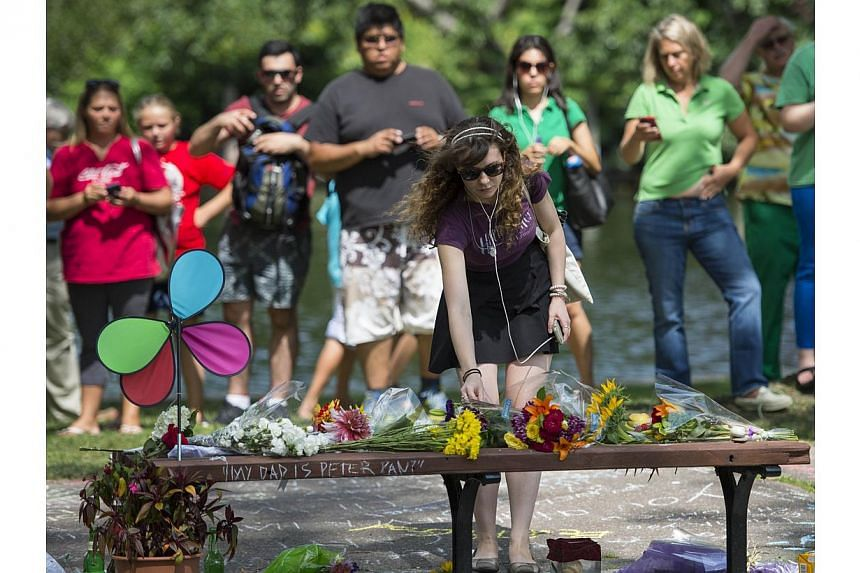 Annie Hochheiser of Cambridge, Massachusetts places flowers onto a fan memorial in honour of Robin Williams on the bench made famous by his movie Good Will Hunting in Boston Public Garden on August 12, 2014 in Boston, Massachusetts. Williams died in