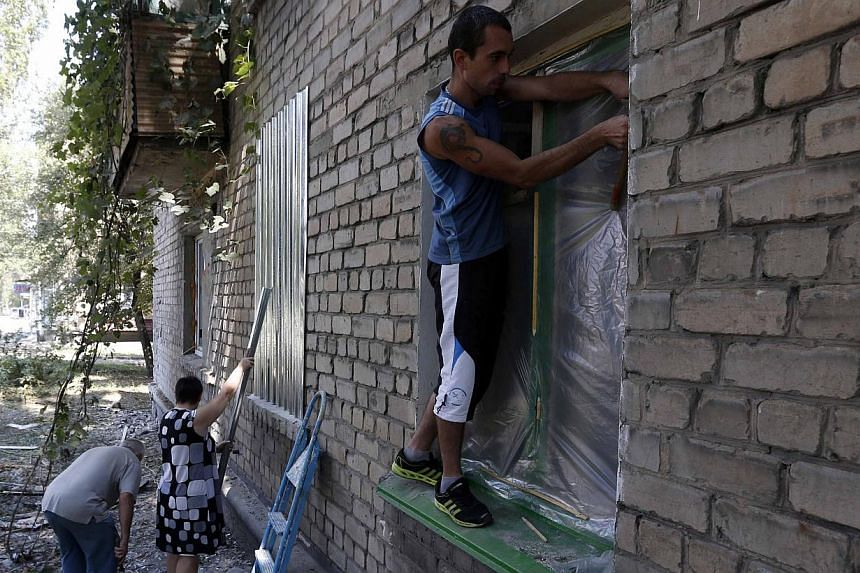 Local residents protect windows with metal shields and plastic in Donetsk August 9, 2014. More than 1,100 people have been killed in the fighting in Ukraine since mid-April, according to the United Nations, in a civil conflict that has dragged ties b