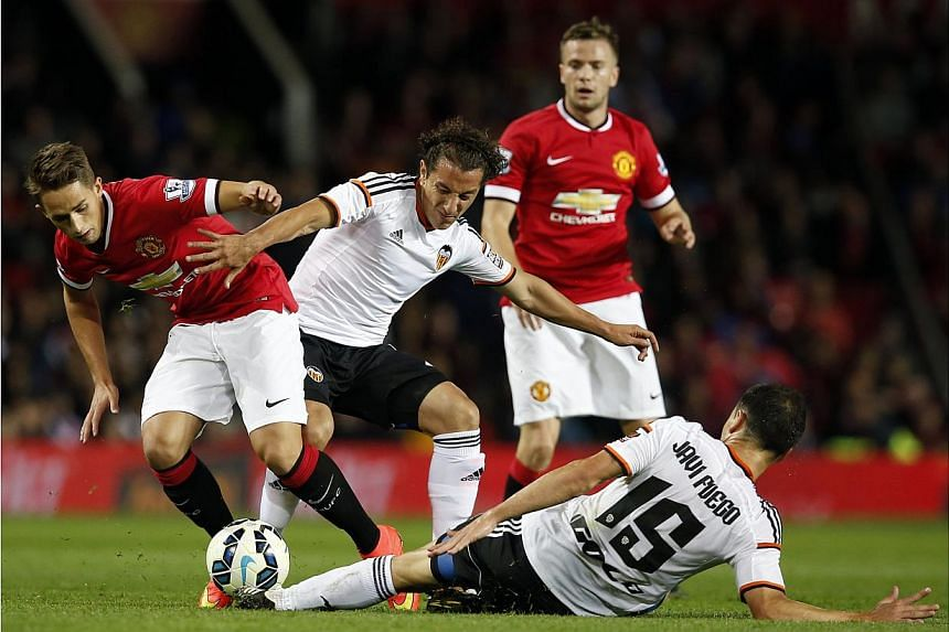 Valencia's Andres Guardado (centre) and Javi Fuego (bottom) challenge Manchester United's Adnan Januzaj (left) during their friendly soccer match at Old Trafford in Manchester, northern England August 12, 2014. -- PHOTO: REUTERS