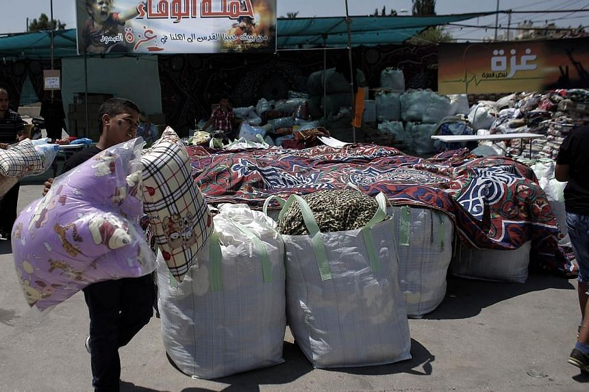Palestinians collect goods and blankets in East Jerusalem, on Thursday, Aug 14, 2014, to be sent and distributed with the Red Cross to people in need in the Gaza Strip.A new, five-day truce between Israel and Hamas appeared to be holding on Thu