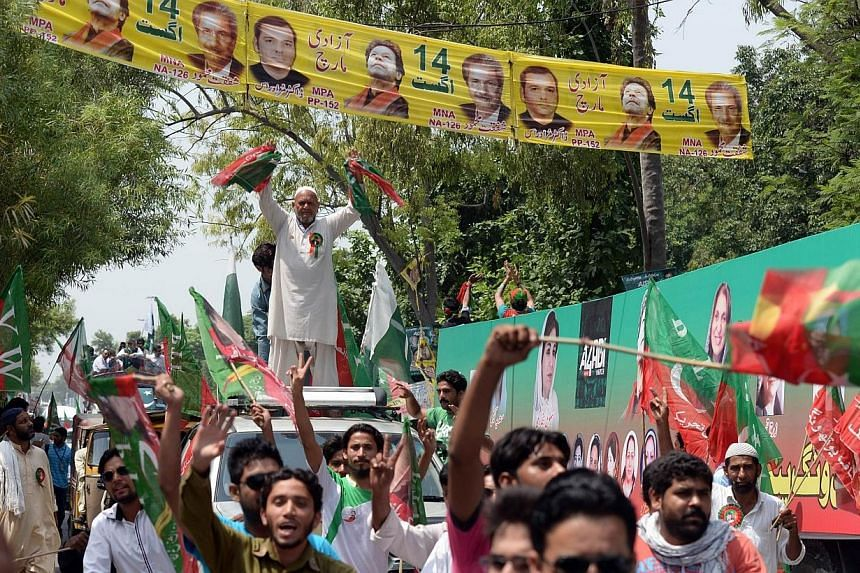 Supporters of cricketer-turned-politician Imran Khan gather outside the residence of Imran before the start of their protest march against government in Lahore on Aug 14, 2014.Thousands of protesters began to march on the Pakistani capital from