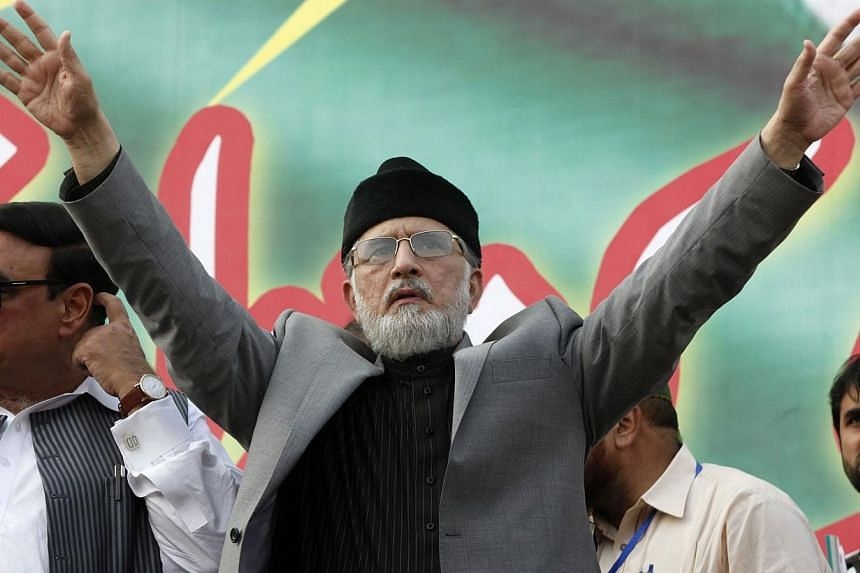 Muhammad Tahir ul-Qadri, Sufi cleric and leader of political party Pakistan Awami Tehreek (PAT), gestures to supporters during a demonstration outside his residence in Lahore on Aug 10, 2014. -- PHOTO: REUTERS